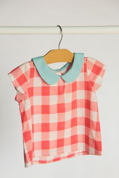 Red gingham with a pale blue peter pan collar. 100% Cotton Wooden button keyhole…