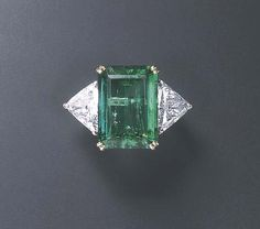 AN EMERALD AND DIAMOND RING, BY HARRY WINSTON  Set with a rectangular-cut emerald, weighing approximately 10.87 carats, flanked on either side by trillion-cut diamonds, mounted in platinum and gold With jeweler's mark for Harry Winston