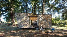 小さな家屋のマイクロキャビンは、溢れた居住空間と登山壁を誇っています