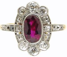 Art Deco Ruby & Diamond Cluster Ring  Art Deco (1920-1935)Item No. 908E A beautiful Art Deco Ruby and Diamond ring set to the centre with a pigeon blood ruby. The centre stone weighs approximately 0.50 ct.