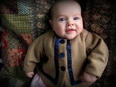 Baby tan wool saque with ribbon trim and covered buttons. Saque coats can be a more practical way of keeping small babies warm at events - they can't kick them off like a blanket!