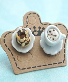 These earrings feature a mismatched pair of handmade donut sculpted from polymer clay along with a miniature coffee cup. Both sits on a scallop edged ceramic plate that measures 1.3 cm in diameter and