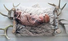 Newborn baby photo posing idea with deer antlers background, faux fur fabric and fawn swaddle blanket