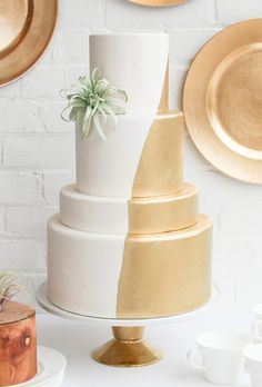 Gold detailing and an air plant adornment give a classic white wedding cake a modern touch.