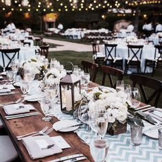 Romance is in the air and in all the details: string lights, long tables, candles and chevron table runners make for a chic rustic wedding reception. | Ten Productions