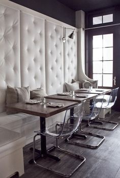Dining space features super tall built-in banquette upholstered in white velvet tufted fabric adorned with vintage grain sack pillows paired with wood top tables and Ikea Tobias Chairs.