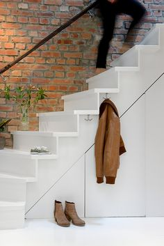 Stark white staircase with embedded hooks for coat storage