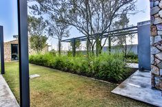 This contemporary farm house was designed around a central courtyard to create privacy. An ode to the farmhouse design, incorporating glass and steel. Courtyards, Farmhouse Design, Bay Window, Facade, Outdoor Living, Pergola, Sidewalk, Contemporary, Create