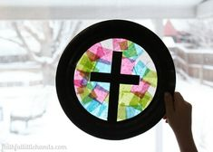 """Celebrate the Resurrection by making """"stained-glass"""" cross suncatchers, a beautiful kids Bible craft for Easter. Perfect for a Sunday school class or a Christian homeschool group."""