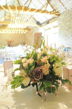 Wedding barn lighting by Oakwood Events and beautiful blooms by That Flower Shop, venue: Notley Abbey, Thame