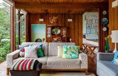 Uma casa toda de madeira e vidro com vista para a copa das árvores e decoração relax.