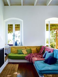 House tour: Marc Newson and Charlotte Stockdale's Greek island escape: The living room in the Stockdale-Newson's Ithaca cottage features brightly coloured handcrafted 'Taki' lounge cushions by Greek furniture design company Coco-Mat, and pieces gathered from the couple's travels.