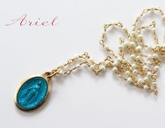Long pearl necklace with a blue medaille miraculouse