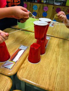 Team-building game for the first day of school. One rubber band with 4-5 strings attached then as a team they must stack the cups.
