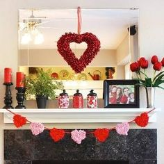 Red pillar candles, roses, and jars of candy complement a store-bought heart wreath on this simple and colorful Valentine's Day mantel. To craft the heart garland, Erin (thesunnysideupblog.com) glued twisted squares of red and pink tissue paper onto cardstock hearts. A family photo adds a nice personal touch./ by phyllis