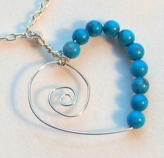 Break out of the red/pink box with a turquoise and silver heart! This silver spiral heart is accented on one side with turquoise colored stone beads.  Materials: Sterling silver chain and wire. Turquoise dyed howlite beads.  Measurements: Chain - 18 inches (46 cm). Heart 1.25 inches (3 cm) wide and long. Beads - 4 mm rounds.