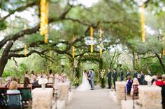 Beautiful daytime ceremony small floral and iron candelabras alternating and beautiful arch with ivory and pink floral Whim Florals Camp Lucy Sacred Oaks Wedding | Shane + Kaci | Dripping Springs Wedding Photography | Al Gawlik
