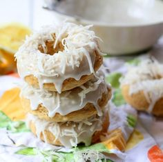 Baked vegan lemon coconut donuts topped with lemon glaze and coconut shreds.