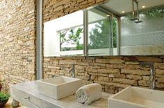 Este es el baño de la suite principal de la Casa Agua del estudio. Una casa proyectada a partir de dos muros que se cruzan revestidos en piedra de laja Neuquén, protagonista principal de este baño.