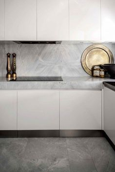 Minimalist kitchen with marble countertops and metallic accents