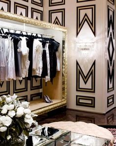 sexy cool dressing room w/gold 'frame' trim, contemporary shapes on wall, black clothing