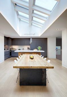 This home features a large wood and steel dining table with the ceiling covered in skylights. Steel Dining Table, Cocinas Kitchen, Kitchen Dinning, Dining Room, Space Kitchen, Cuisines Design, Minimalist Home, Kitchen Interior, Studio Interior