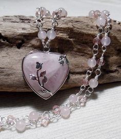 Rose Quartz Heart and Crystal Necklace 26 long in silver  This beautiful necklace features a Genuine Rose Quartz Gemstone that has been set in a Sterling Silver (925) setting with two beautiful roses. The Rose Quartz itself is heart shape that measures 30mm x 30mm and hangs from a handmade 26 chain. The chain is made by individually wire wrapping Genuine Rose Quartz beads and Vintage Rose Swarovski Crystals. Each bead and crystal is then wire wrapped to each other to create a chain that is…