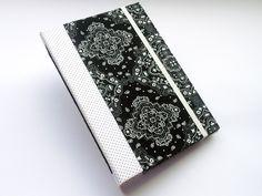 Caderno A5, com 96 folhas, produzido manualmente. Capa dura revestida em tecido estampado e fechamento em elástico. Costura correntinha feita em fio encerado. <br> <br>Dimensões aproximadas: 22cm x 15,5cm