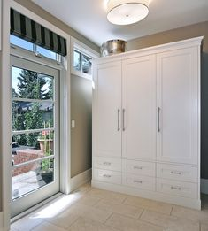ikea pax wardrobe Transitional Entry Designs Calgary brick ceiling lamp closet gray hammered metal limestone mud room patio door roman shade storage striped shade tile floor transom window