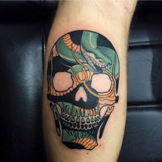 the red balls skull and snake tattoo highlights the beefy calf