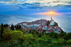 Sun aligns with the Church of St. George in the coastal jewel town of Piran, Slovenia