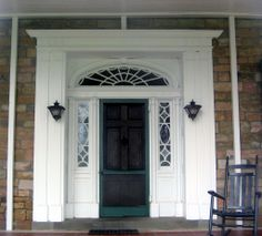 Federal Colonial door surround with elliptical spiderweb fanlight and egg and dart sidelights.