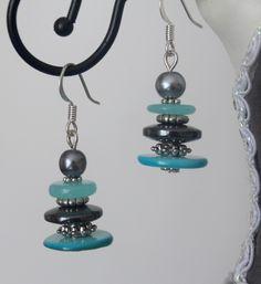 Boucles d'oreilles gris bleu nacre perle magique. Boucles d'oreilles composé d'une perle magique grise, d'un palet en verre bleu turquoise, d'un palet anthracite, et d'un palet en nacre turquoise. Le tout séparé par des apprêts en métal argenté. Jewelry Design Earrings, Wire Jewelry, Jewelry Crafts, Beaded Jewelry, Jewellery, Button Earrings, Wire Earrings, Seashell Jewelry, Bleu Turquoise