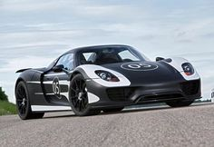 Porsche 918 Spyder prototype returns to the road with polished black and white shell...  Porsche's 918 plug-in hybrid flexes its 770 horse power for the camera. The $845,000 machine pairs a combustion engine with electric motors to achieve 78 mpg consumption rating, and sports a carbon-fiber reinforced-plastic monocoque (self-supporting) shell, rear-axle steering and that unique upward-venting exhausted system. Production starts September 2012.