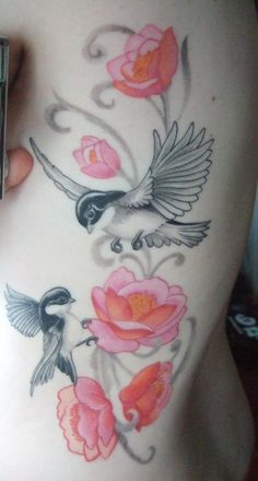 Pretty black & gray birds with colored flowers tattoo.