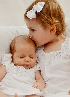 Princess Estelle of Sweden snuggles her cousin Princess Leonore in an an official photo release the the Swedish royal house and Princess Madeleine 4/24/2014