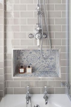 We love the blue mosaic niche with the grey subway tiles in this shower.
