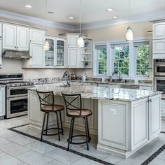 The light and bright chef's kitchen with white cabinets, granite countertops, tile flooring, top of the line appliances, large center island, pendant lights, breakfast area, and butler's pantry lead onto an expansive deck overlooking the lush green lot. Listed by The Casey Samson Team in Oakton, VA a Wall Street Journal Top Team in Northern Virginia.