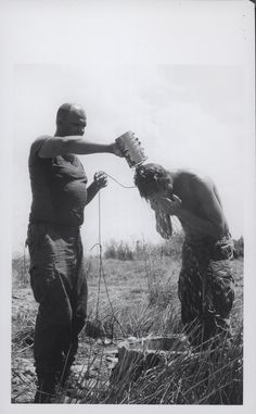 """Robert Williams Cools Off With Help From Richard Marurer, 1969 """"Cooling Off: Marine Lance Corporal Robert D. Williams, 21 (Boise, Idaho) cools off as Gunnery Sergeant Richard H. Marurer (Whitehall, Michigan) pours some cool water over him during a break on Operation Pipestone Canyon. The two Marines are members of the 1st Marine Division's 1st Marine Regiment, which along with other Marine units, Republic of Vietnam forces, and Republic of Korea Marines, is clearing the area of Viet Cong and…"""