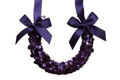This horseshoe is created using an authentic traditional light-weight horsehoe, which has been hand-wrapped in aubergine purple beaded and sequin tulle; and adorned with two purple silk satin bows.