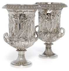 A LARGE AND IMPOSING PAIR OF GERMAN SILVER PLATED ON COPPER WINE COOLERS MARK OF WMF, CIRCA 1890 Of campana form, the sides applied with a frieze of Classical ladies at various artistic pursuits including: dancing, acting and playing music, all below a fruiting vine, the lower bodies decorated with acanthus leaves, on fluted circular bases, detachable liners.