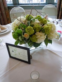 White hydrangea, green vibernum, ivory roses, variagated pittosporum, curly willow in a square glass vase Designed By: hillside-consultants.com