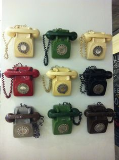 Collection of old rotary dial phones. Wall display, multiple colours Repinned by www.silver-and-grey.com