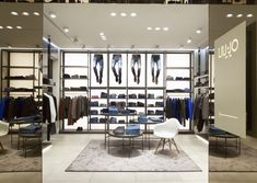 """Gray marble, nichel chrome and neutral wood surround the focus backlighted denim wall. Last but not least the """"home"""" touch is brought by the Eames armchair and living oriented multilevel table system."""