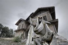 Haunted house. Abandoned and ruined manor with a gream reaper statue in foreground - http://places2seebeforeyoudie.com/haunted-house-abandoned-and-ruined-manor-with-a-gream-reaper-statue-in-foreground/