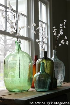 love this demijohn bottle collection with spring flower stems from World Market eclecticallyvintage.com