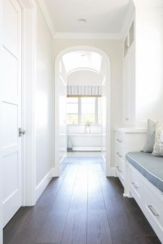 Long walk through closet features a built-in window seat flanked by floor to ceiling built-in cabinets