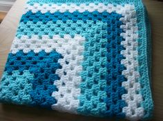 Hand crocheted baby blanket in white and light and deep turquoise. Great colours for a unisex blanket. Size is 28 x 28 inches which is perfect for a