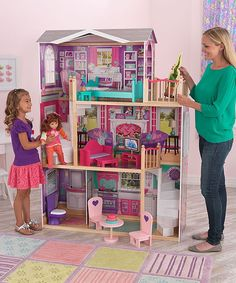 WOW... look at this doll house! It is huge and looks like the little girl has a doll the size of an American Girl Doll.