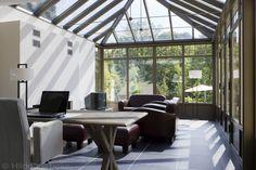 Grote aluminium orangerie met gezellige zithoek met open haard en bureau, aluminium veranda bouwen | De Mooiste Veranda's